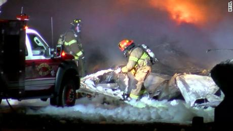 Firefighters tend to flames at the scene of a plane crash Wednesday morning east of Toledo's airport.