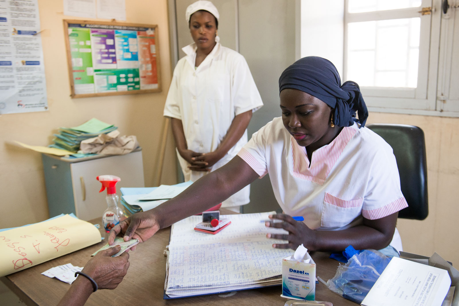 Chief midwife Penda Ba returns Awa's ID card following her mandatory check-up