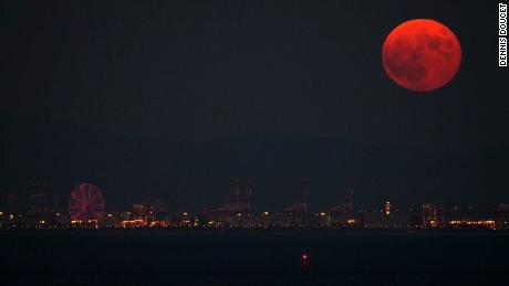 "Doucet took this image in 2015 that shows the ""blood"" moon rising above Osaka, Japan."