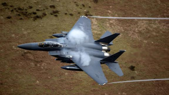 A United States Air Force F-15 fighter jet based at RAF Lakenheath speeds through the Dinas Pass, known in the aviation world as the Mach Loop in Dolgellau, Wales.