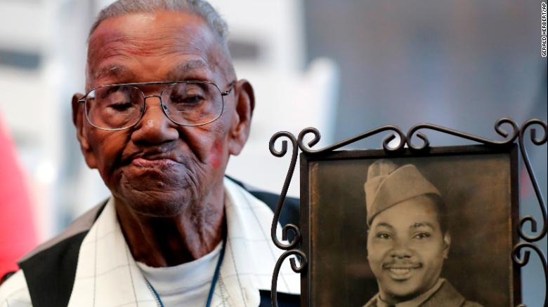 World War II veteran Lawrence Brooks holds a photo of him taken in 1943.