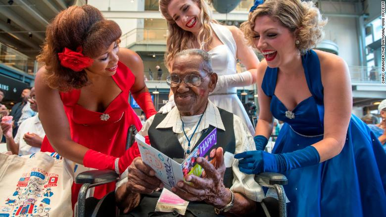 Singing group The Victory Belles give World War II veteran Lawrence Brooks a birthday card.