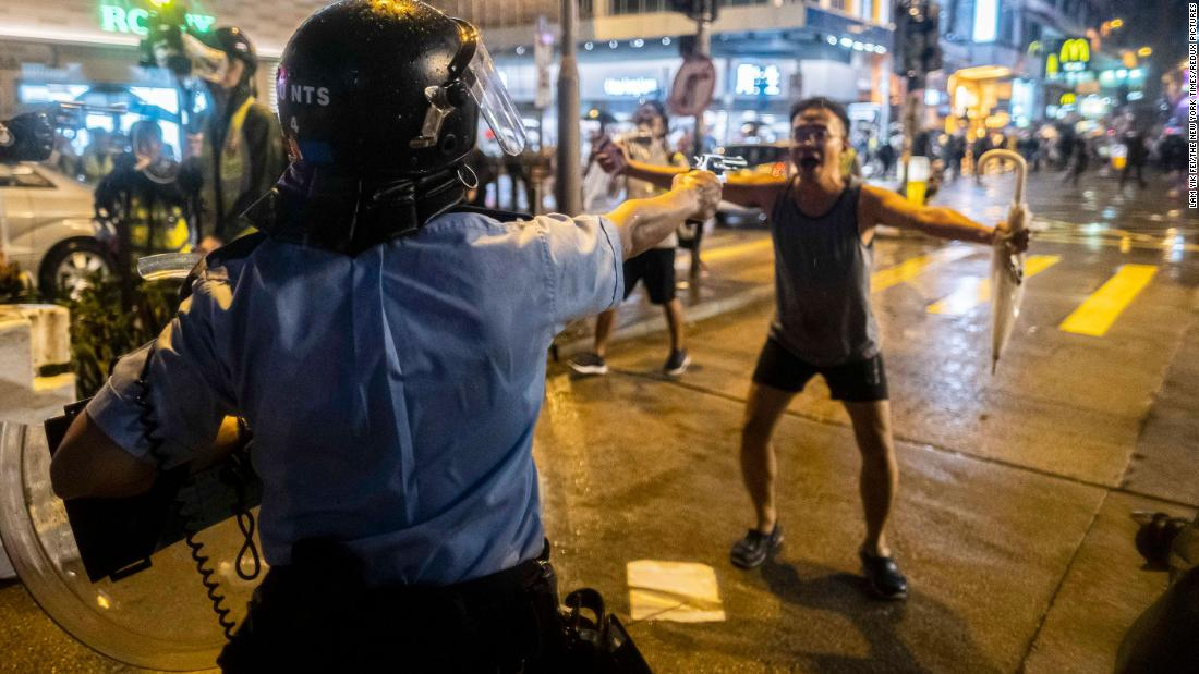 A police officer aims a gun in front of a protester on August 25.