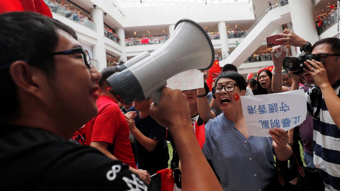 "Pro-government and anti-government supporters chant against one another at a shopping mall in Hong Kong on Friday, September 13. The sign translates to ""Stop violence and curb chaos; safeguard Hong Kong."""