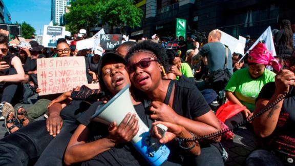Women cry in front of the Johannesburg Stock Exchange on September 13, 2019, during a protest against the abuse of women in South Africa.