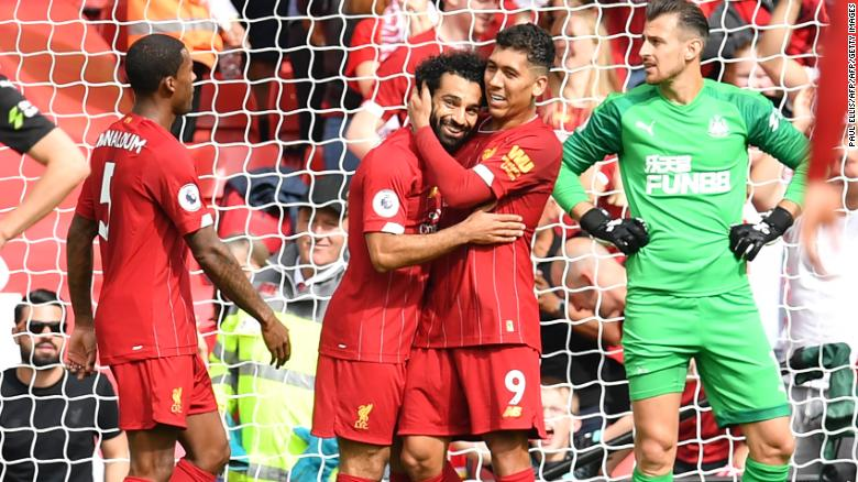 Mohamed Salah and Roberto Firmino celebrate Liverpool's third goal.