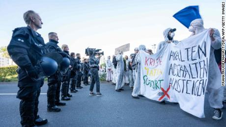 Demonstrators from the action group Sand im Getriebe (Sand in the Gearbox) faced police officers as they blocked a road in Frankfurt.