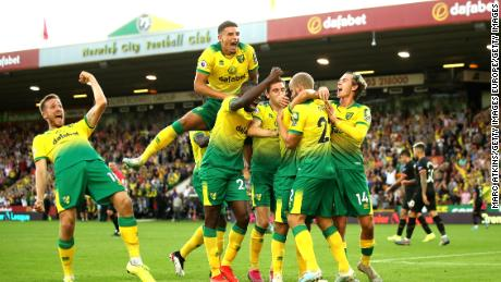 Teemu Pukki of Norwich City celebrates with teammates after scoring his team's third goal during the Premier League match between Norwich City and Manchester City at Carrow Road on September 14, 2019.