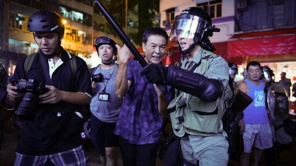 A pro-China supporter, center, is escorted by police after confronting journalists in Hong Kong on September 15.