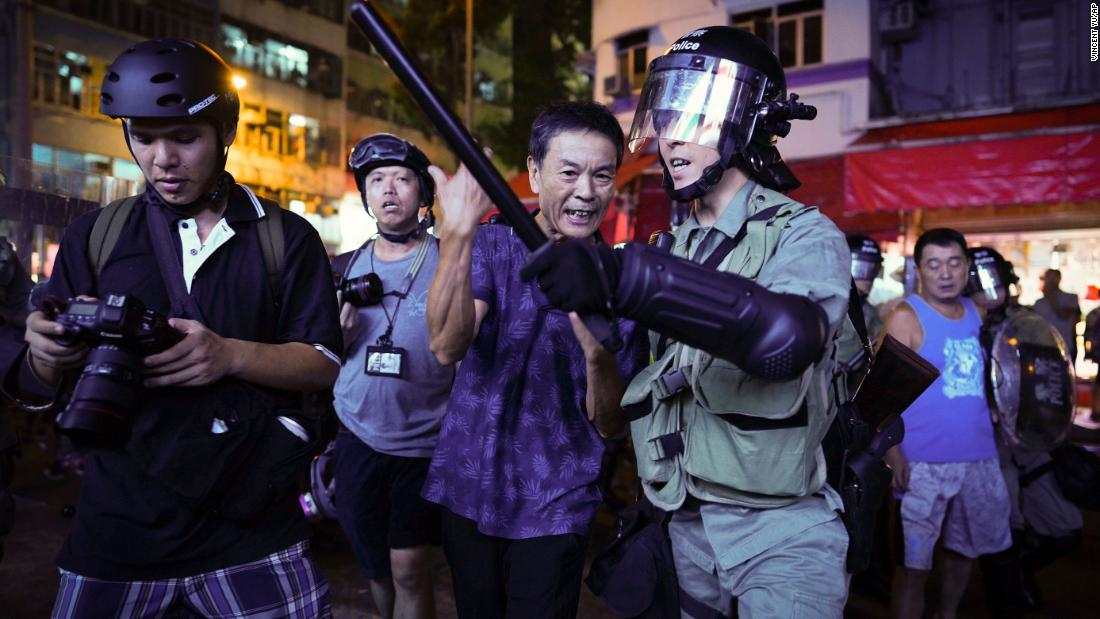 A pro-China supporter, center, is escorted by police after confronting journalists in Hong Kong, on September 15.