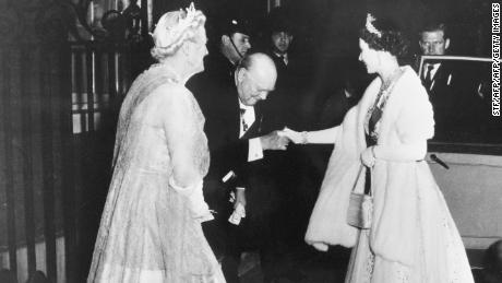 Winston Churchill kisses Queen Elizabeth II's (R) hand as she leaves 10 Downing Street in 1955.