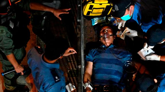 A man is seen to as he lies injured after he was surrounded and beaten on a street in North Point in Hong Kong on September 15, 2019.
