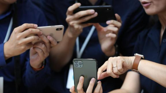 CUPERTINO, CALIFORNIA - SEPTEMBER 10: Attendees look at the new Apple iPhone 11 Pro during a special event on September 10, 2019 in the Steve Jobs Theater on Apple