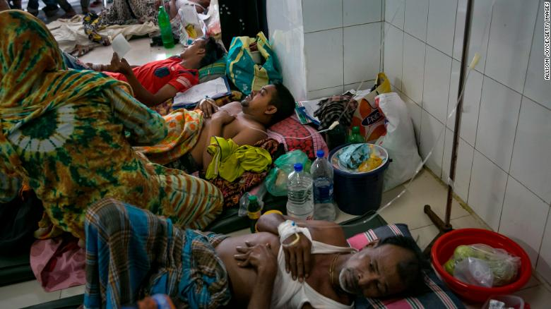 Bangladeshi patients suffering from dengue fever rest on the floor of a hospital ward in Dkaha.