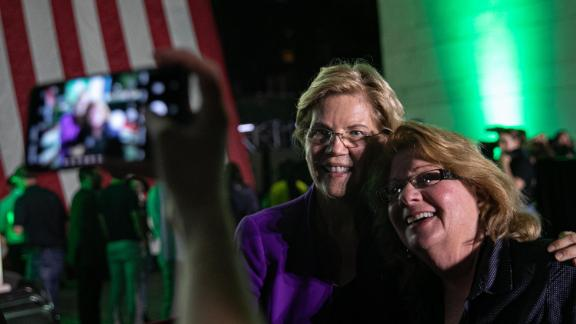 Senator Elizabeth Warren, a Democrat from Massachusetts and 2020 presidential candidate, center, poses for a photograph with a supporter during an event at Washington Square Park in New York, U.S., on Monday, September 16, 2019. Warren rolled out a sweeping anti-corruption plan Monday that would toughen rules for wealthy and influential figures seeking to influence policy, hours before she intends to pitch it to voters in Wall Streets back yard.