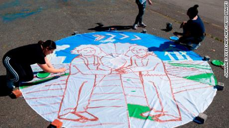 Children paint on a parachute made out of paper in New York City ahead of the September 20th Youth Climate Strike.