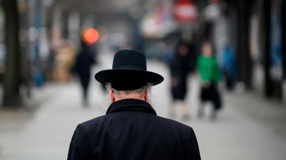 A Jewish man crosses a street in a Jewish quarter in Williamsburg, Brooklyn, on April 9, 2019 in New York City.