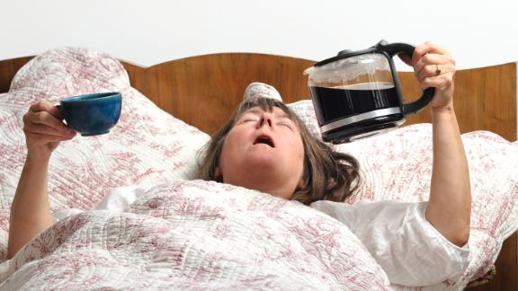 Woman too tired to wake up, holding coffee jug and cup. Could be used to show unhealthy lifestyle, tiredness, stress, sleep problems or bad home-work balance