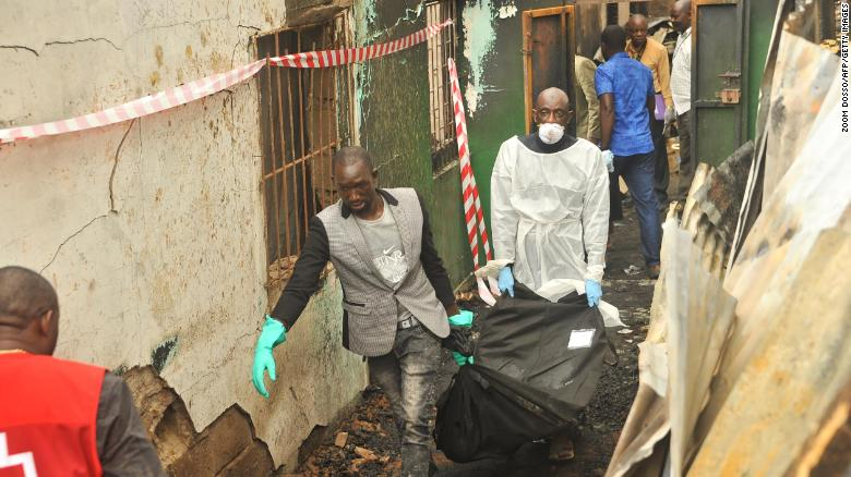 Rescuers hold a body after an overnight fire at the school that killed at least 26 children and two teachers in Monrovia, Liberia on Wednesday.