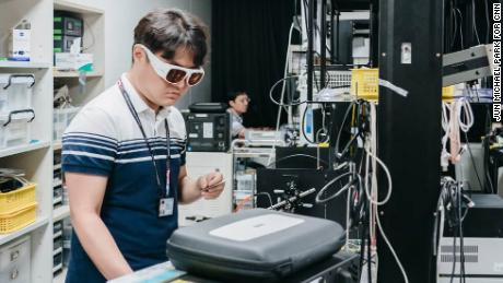 Engineers of Samsung's Mobile Healthcare Lab wear protective goggles while working with lasers.