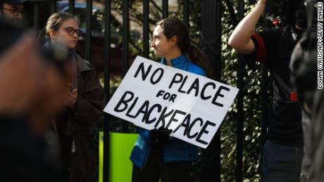 "Protestors rally against Virginia Governor Ralph Northam outside of the governors mansion in downtown Richmond, Virginia on February 4, 2019. - Demonstrators are calling for the resignation of Virginia Governor Ralph Northam, after a photo of two people, one dressed as a Klu Klux Klan member and a person in blackface were discovered on his personal page of his college yearbook. Northam said that while he had not appeared in the photo, ""many actions that we rightfully recognize as abhorrent today were commonplace"" and he was not surprised such material made its way to the yearbook. (Photo by Logan Cyrus / AFP)        (Photo credit should read LOGAN CYRUS/AFP/Getty Images)"
