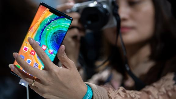 19 September 2019, Bavaria, Munich: A woman photographs the Huawei Mate 30 Pro smartphone after a Huawei press conference. Huwaii has introduced the new smartphone series Mate 30 / 30 Pro. Photo: Sven Hoppe/dpa (Photo by Sven Hoppe/picture alliance via Getty Images)