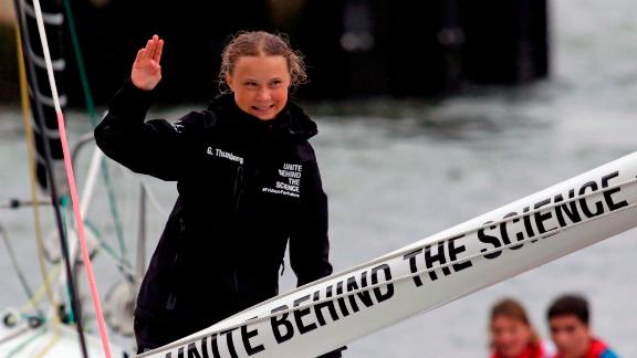 Greta Thunberg waves to crowds waiting for her at the end of a 15-day Atlantic crossing in a zero-carbon yacht.
