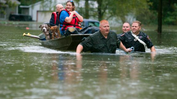 Police pull a boat carrying residents Thursday from their flooded neighborhood in Splendora, Texas.