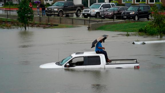 A man sits on top of a truck on a flooded road Thursday in Houston. Members of the Houston Fire Department gave him a life jacket and walked him to dry land.