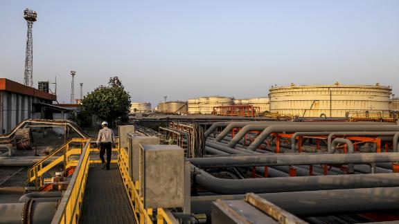 Storage tanks stand beyond pipework at the Vadinar Refinery complex operated by Nayare Energy Ltd., formerly known as Essar Oil Ltd. and now jointly owned by Rosneft Oil Co. and Trafigura Group Pte., near Vadinar, Gujarat, India, on Thursday, April 26, 2018. The refinery was the crown jewel in a blockbuster $13 billion acquisition that, at the time, represented the largest foreign direct investment in India