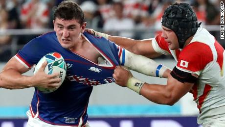 Russia's Nikita Vavilin, center, is tackled by Japan's Pieter Labuschagne during the Rugby World Cup Pool A game at Tokyo Stadium between Russia and Japan in Tokyo, Japan, Friday, Sept. 20, 2019. (AP Photo/Eugene Hoshiko)