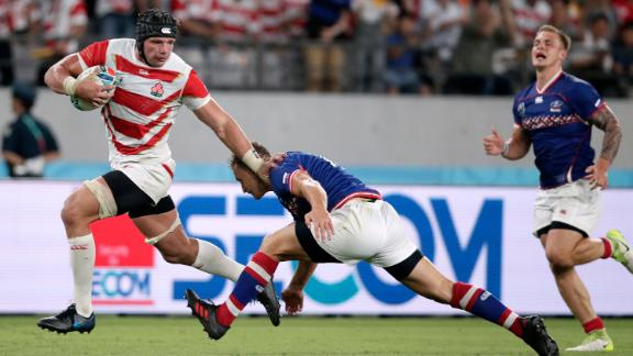 Japan's Labuschagne, left, fends off Russia's Yury Kushnarev on his way to scoring the Brave Blossom's fourth try.