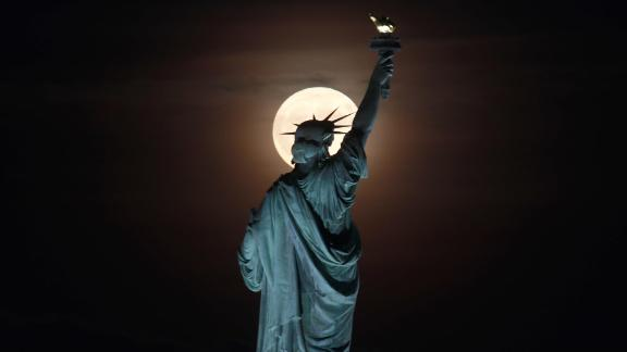 JERSEY CITY, NJ - SEPT 13: The full Harvest Moon rises behind the Statue of Liberty in New York City on September 13, 2019 as seen from Jersey City, New Jersey. (Photo by Gary Hershorn/Getty Images)