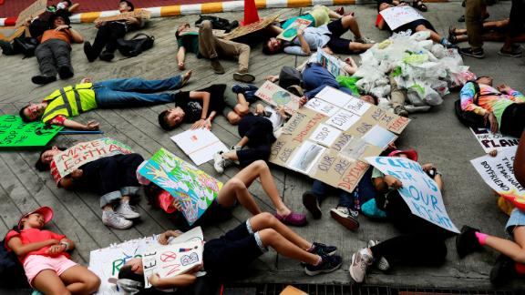 Protesters lie on the ground near the Ministry of Natural Resources and Environment in Bangkok.