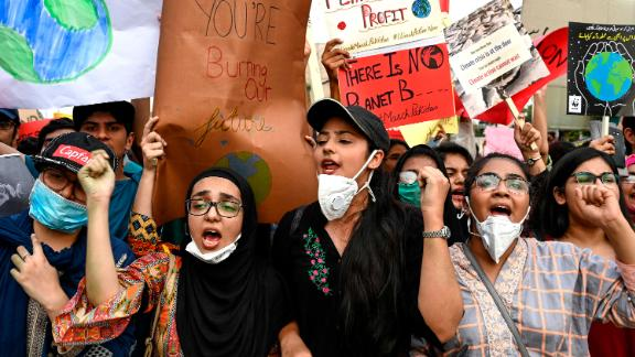 People hold placards as they march in Lahore, Pakistan.