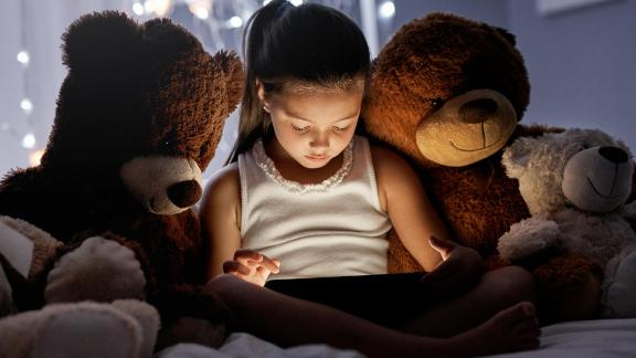 Shot of an adorable little girl using a digital tablet in bed at night