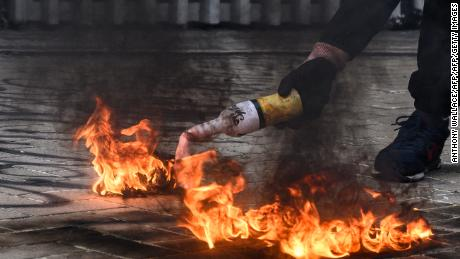 A protester uses a fire to light up a molotov cocktail before throwing it towards police stationed outside the government headquarters in Hong Kong on September 15, 2019. - Hong Kong riot police fired tear gas and water cannon at hardcore pro-democracy protesters hurling rocks and petrol bombs on September 15, tipping the violence-plagued city back into chaos after a brief lull in clashes. (Photo by ANTHONY WALLACE / AFP)        (Photo credit should read ANTHONY WALLACE/AFP/Getty Images)