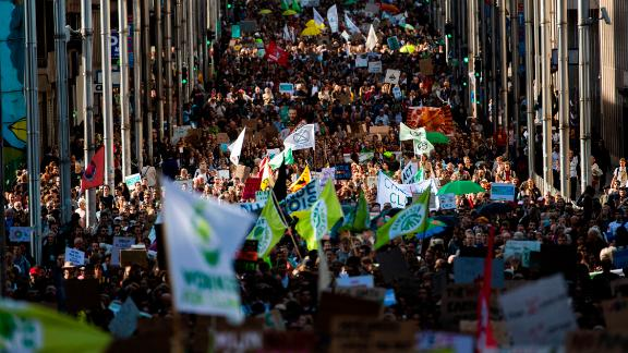 Thousands crowd a street during a climate protest in Brussels.