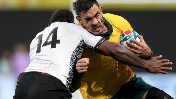 Also on Saturday, Australia beat Fiji 39-21. Adam Coleman of Australia is tackled by Josua Tuisova during their Group D game between Australia and Fiji at Sapporo Dome.
