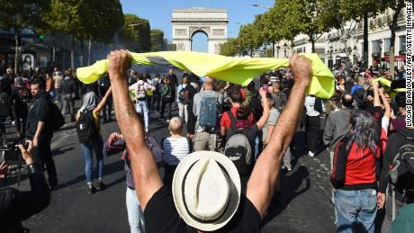 A protester holds up a yellow vest in front of the Arc de Triomphe on the Champs-Élysées Saturday.