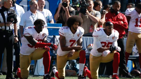 Colin Kaepernick, middle, and members of the San Francisco 49ers kneel during the national anthem prior to the game against the Seattle Seahawks at CenturyLink Field on September 25, 2016.
