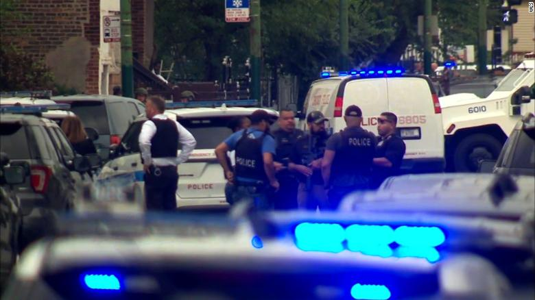 Police officers gather near the site where a Chicago officer was shot Saturday morning.