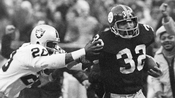 Franco Harris (32) eludes a tackle by Oakland Raiders' Jimmy Warren as he runs for a touchdown in an AFC Divisional game in January 1972.