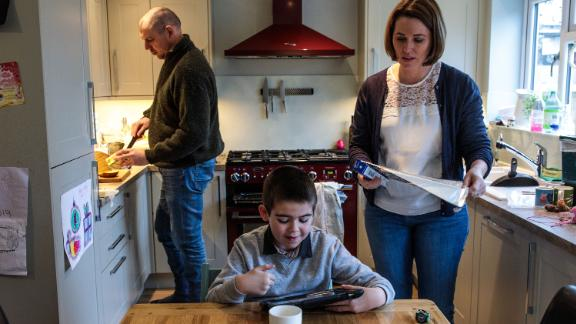 Alfie Dingley watches a video on a tablet as his parents Drew Dingley and Hannah Deacon prepare lunch at their home on January 13, 2019 in Kenilworth, England.