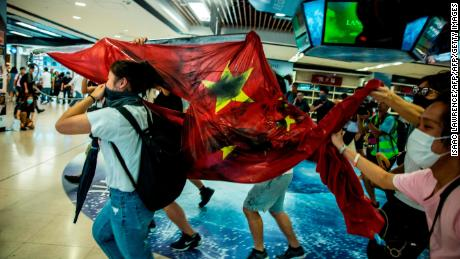 Pro-democracy protesters desecrate the Chinese national flag during a protest at the New Town Plaza shopping mall in Hong Kong's Sha Tin district on September 22, 2019. - The demonstrators rallied inside a mall on September 22, with some activists vandalising a nearby subway station and defacing a Chinese flag, but plans to disrupt the airport did not materialise. (Photo by Isaac LAWRENCE / AFP)        (Photo credit should read ISAAC LAWRENCE/AFP/Getty Images)