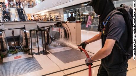 A protester uses a fire hose during a demonstration inside a shopping mall in Shatin district on September 22, 2019 in Hong Kong.