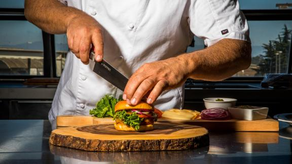 "Moss Landing, CA - September 5, 2019: Chef Tucker Bunch prepares Sweet Earth's ""Awesome Burger"" in the test Kitchen at their Moss Landing headquarters."