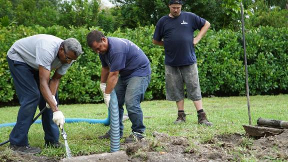 Septic tank repair workers flush out a septic system in Miami.