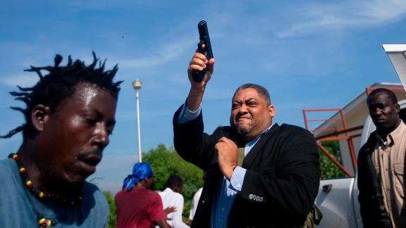 Haitian Senator Ralph Fethiere fires a gun outside parliament in Port-au-Prince, Haiti on Sept. 23, 2019.