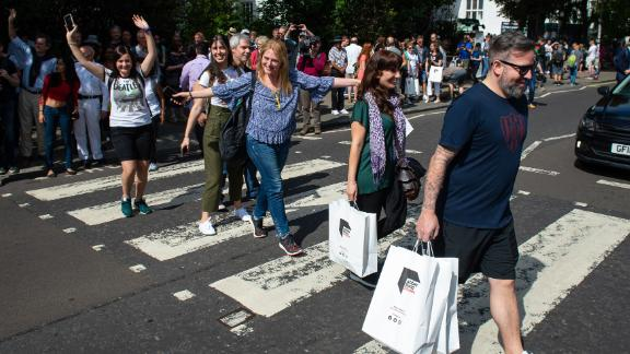 Beatles fans walk across the Abbey Road crossing in London on August 8, 2019, to mark the 50th anniversary of the eponymous album's release.